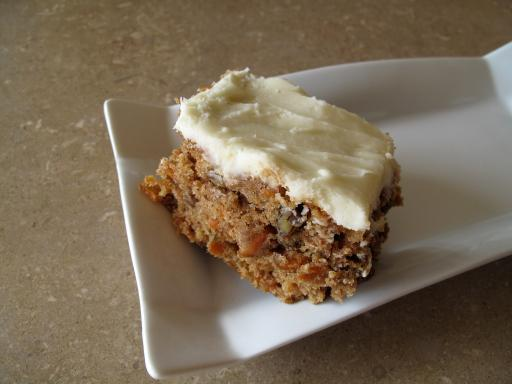 A Plate with a Slice of Fully Loaded Carrot Cake with cream cheese buttercream icing on top