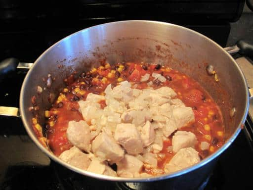 chicken/onion combo added to the pot with tomatoes