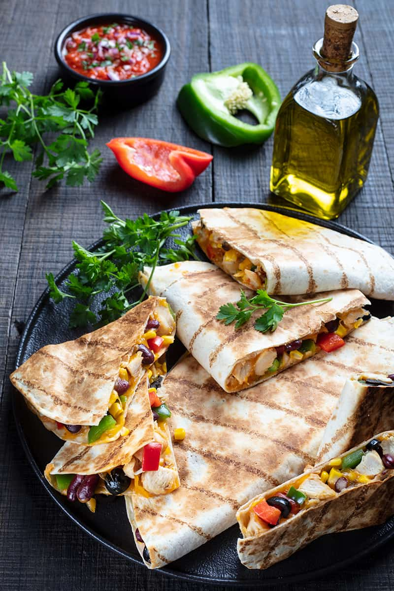 stack of Quesadillas in a large black serving plate garnish with parsley leaves, sliced green and red peppers, oil in bottle and dipping sauce on its background