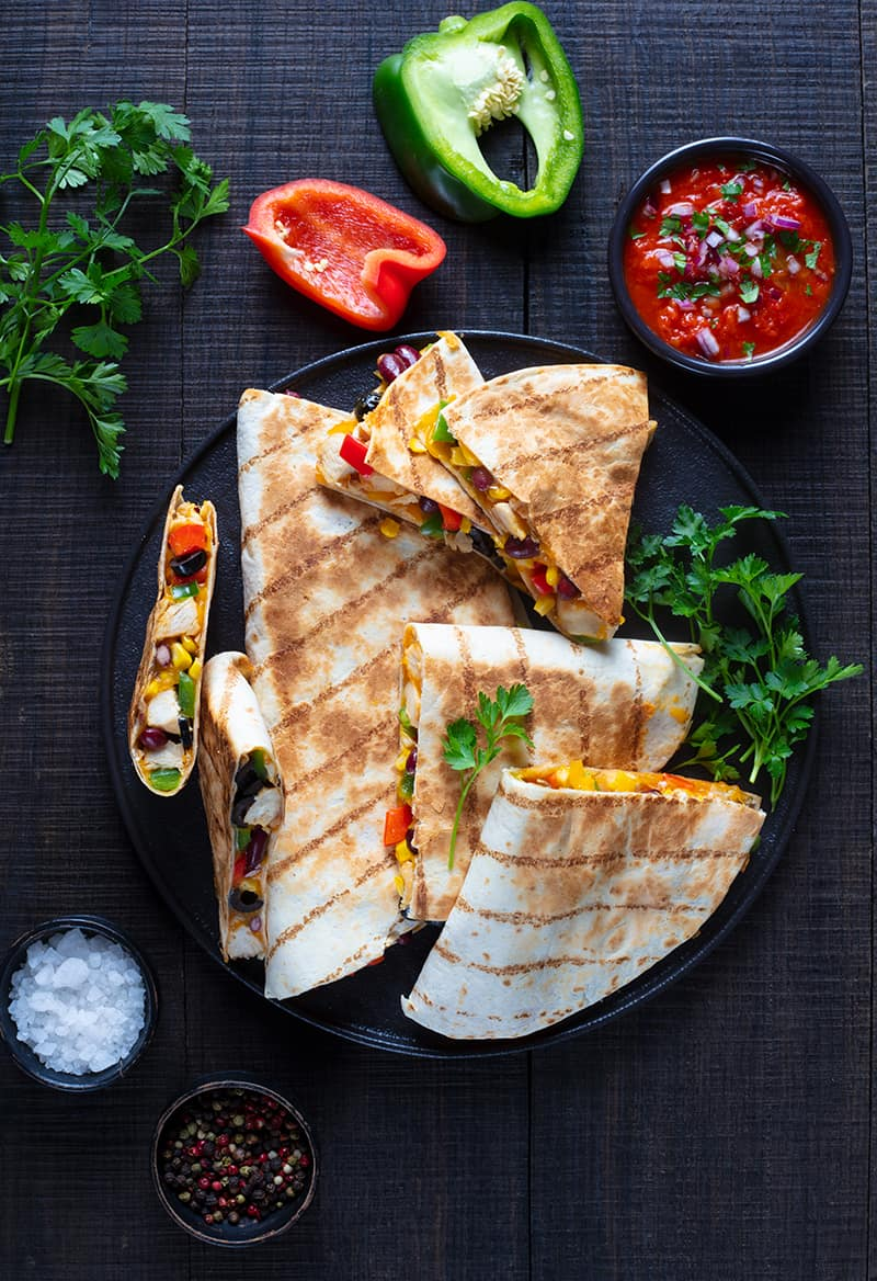 stack of Quesadillas in a large black serving plate garnish with parsley leaves, dipping sauce, slice of red and green peppers beside the plate