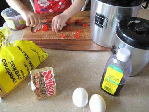 Ingredients needed for Chocolate Cherry Squares in the table with a child chopping the cherries