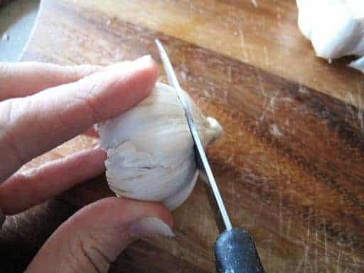 Slicing the top off the garlic head until the cloves are exposed