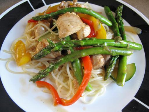 Close up of A Plate with Chicken Asparagus Stir Fry Over Angel Hair Pasta