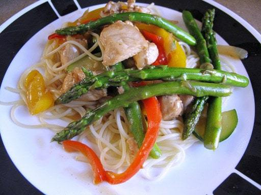 A Plate with Chicken Asparagus Stir Fry Over Angel Hair Pasta