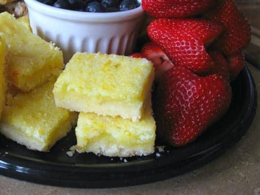 black plate with lemon bars and fresh berries
