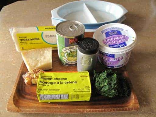 All the ingredients needed in making Spinach Artichoke Dip in a wooden tray