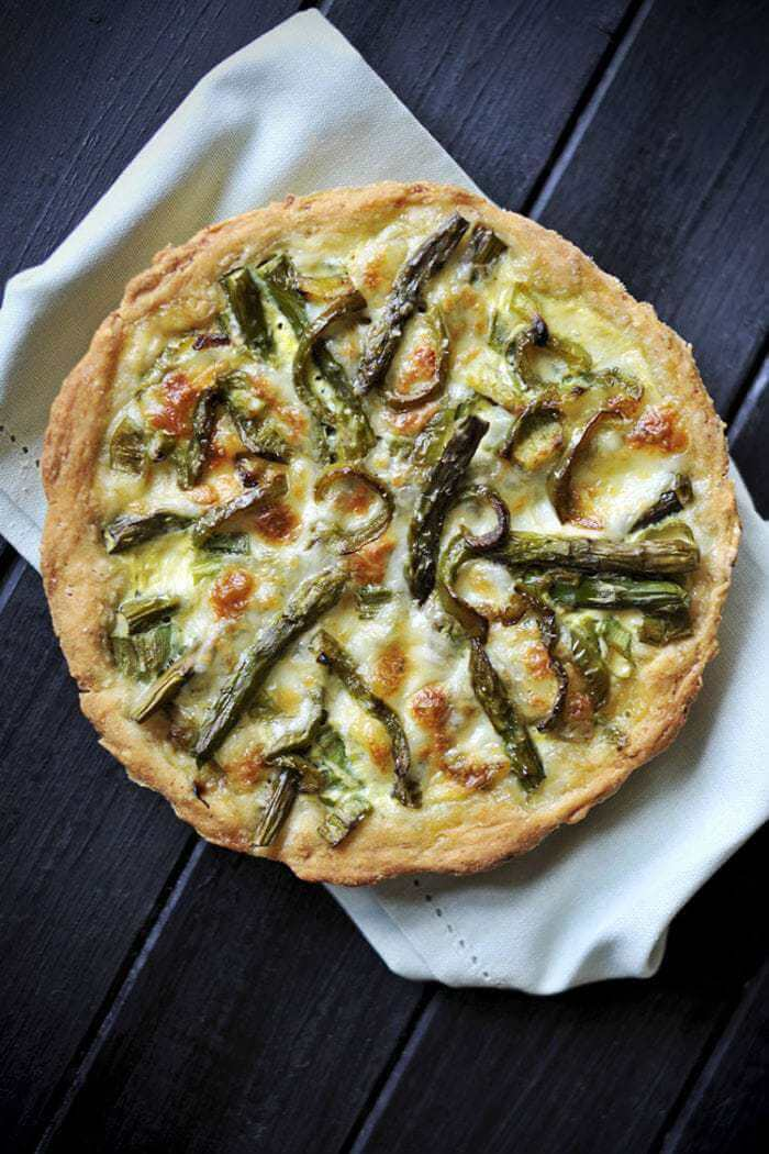 white cloth underneath a whole Swiss Mushroom Asparagus Quiche on a dark wood background