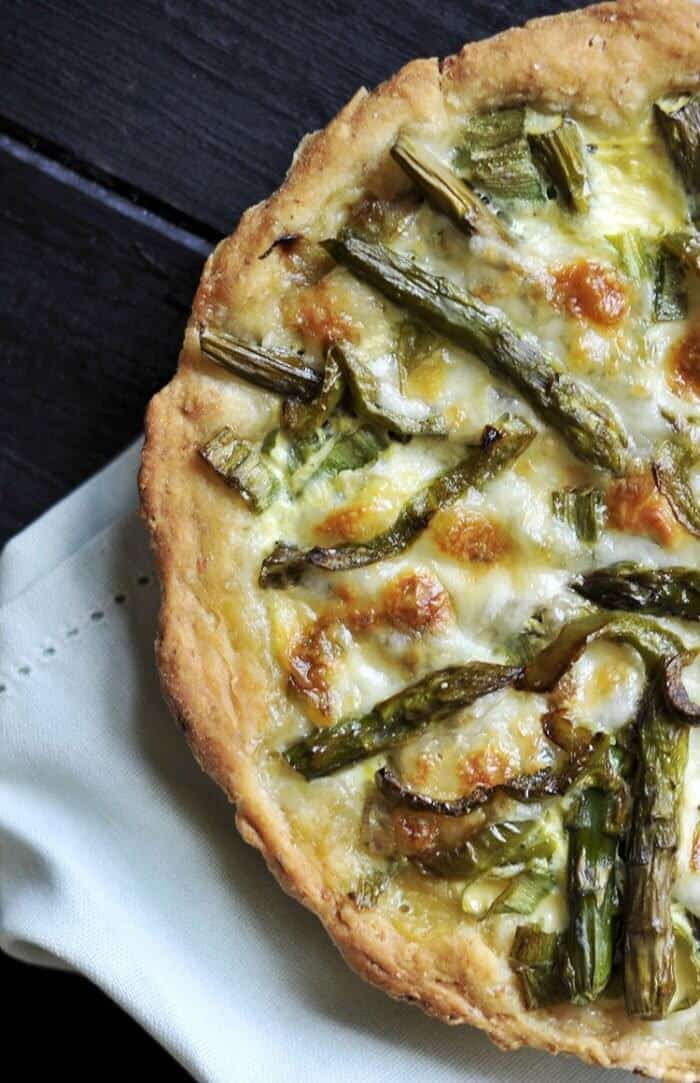 close up Swiss Mushroom Asparagus Quiche with lovely pasta crust on a white cloth and dark wood background