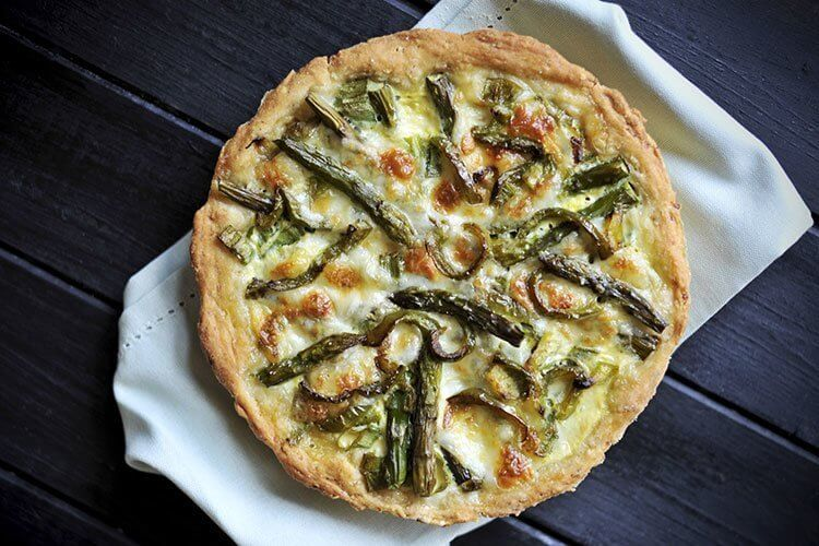 a whole Swiss Mushroom Asparagus Quiche on a white kitchen cloth