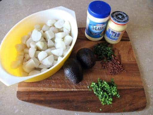 all the ingredients needed for Herbed Potato Salad With Avocado on a wood board