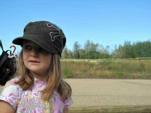 little girl wearing black cap looking sideways