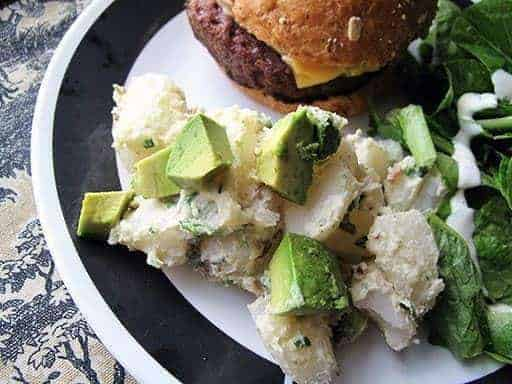 Herbed Potato Salad With Avocado chunks on a white plate with black design