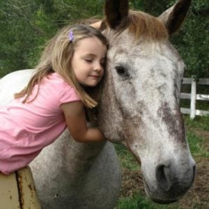 little girl hugging the horse