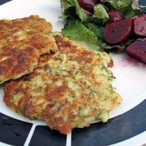 2 pieces Fried Zucchini Cakes in a plate with chunks of beets on side
