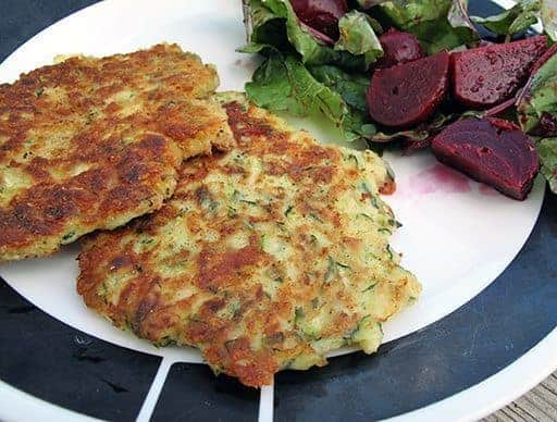 Crispy and crunchy Fried Zucchini Cakes in white plate with beet salad on side