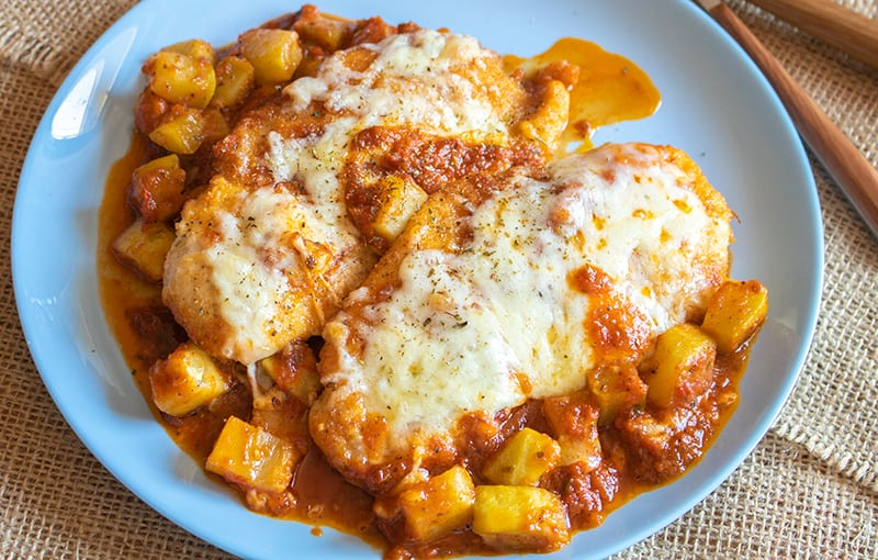 a plate of Chicken Parmigiana with sauce and vegetables