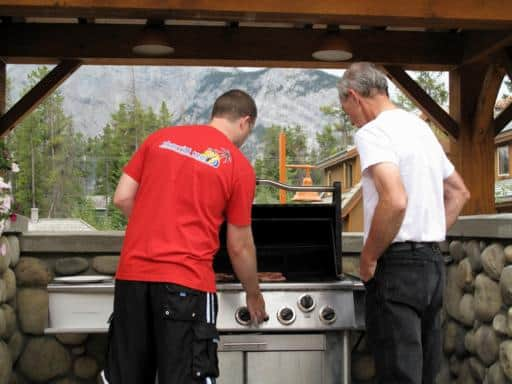 two men on the barbeque to cook some delicious rib eye steaks