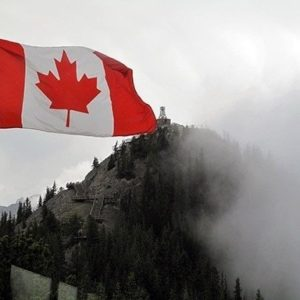 close up waving Canadian flag with the view of mountain