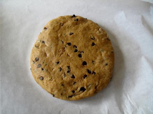 a piece of Pumpkin Scones dough flatten into a circle on a parchment paper