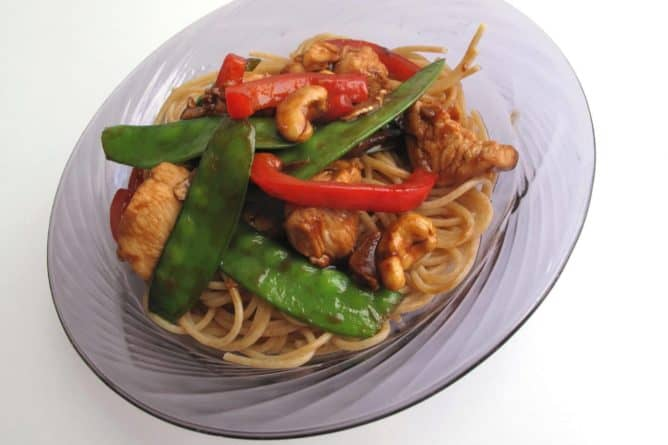 a plate of Cashew Chicken Stir Fry over vermicelli noodles on white background
