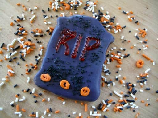 blue chocolate sugar cookies with letters letters of RIP and colorful sprinkles around