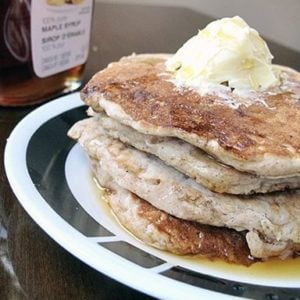 stack of Apple Pie Pancakes in a plate, a bottle of maple syrup on background