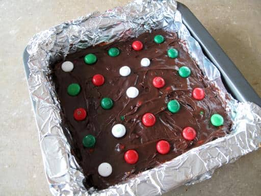 baking pan with tinfoil and mixture of M&M's Fudge ready to refrigerate