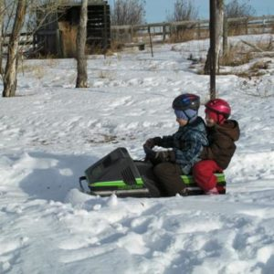 young siblings riding a single Ski-Doo