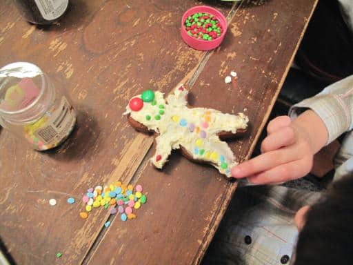 adding decoration to a gingerbread man cookie