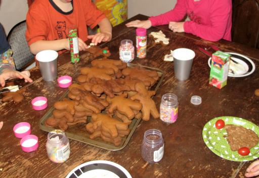 Gingerbread cookies in a tray at the middle of the table, icing and sprinkles on the sides