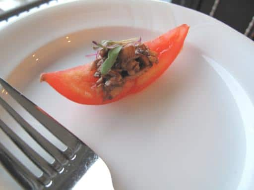 slice of tomato with mona mushroom in a white plate