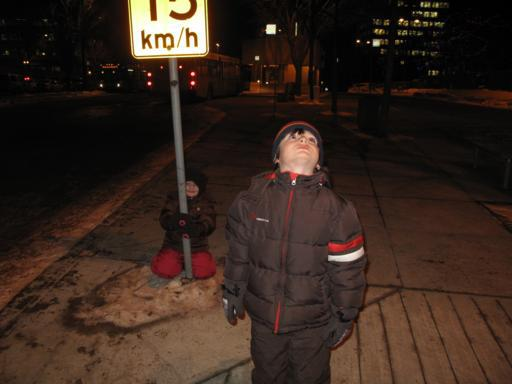 kid wearing winter jacket standing and looking up, another kid on his back holding in road sign