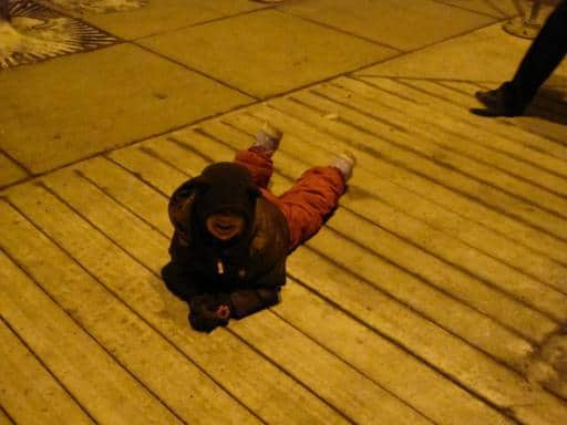 a kid wearing winter coat laying on his stomach