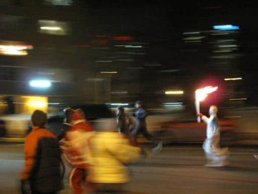 man in white spandex carrying a flame stick