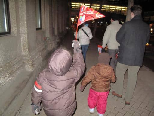 kid in winter coat holding a red flaglet