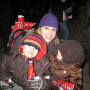 Mom with her two kids sitting in the street wearing winter coats and beanie hats