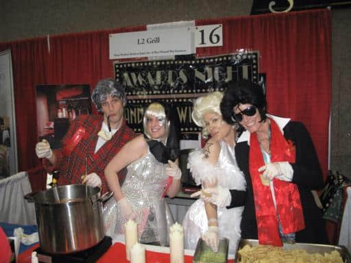 group photo in the booth of L2 Grill, two women wearing white dresses and two man wearing red and black on their sides