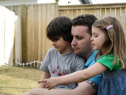 Dad with his kids watching the fire pit avidly