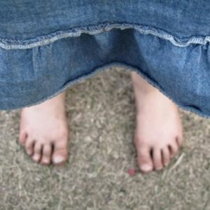 dirty feet of a little girl wearing a denim dress