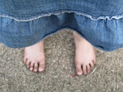dirty feet of a little girl wearing a denim dress
