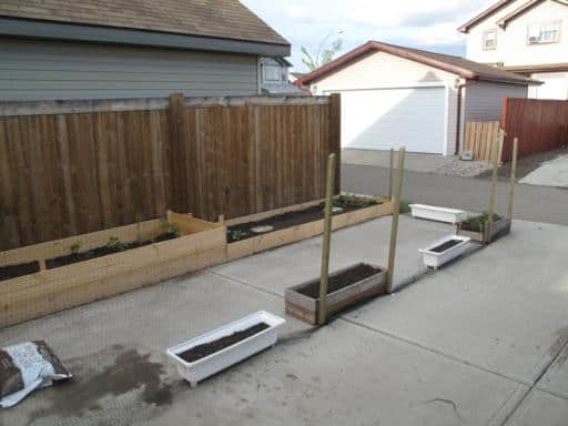 garden beds on the side of the fence and planting pots