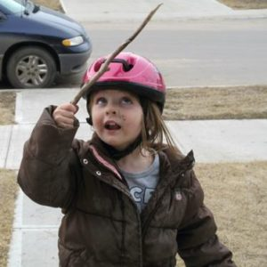 little girl wearing pink bike helmet and brown winter jacket holding a stick