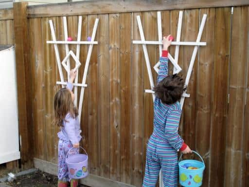 two little kids wearing their jammies reaching for the eggs in the fence