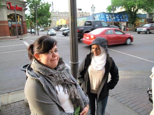 woman with a scarf on her neck, standing near the light post in the street
