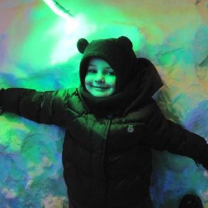little girl wearing winter coat posses on the wall with green paint