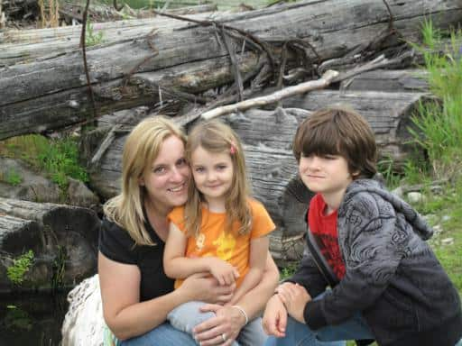 Mom and her kids sitting with the background of big tree logs