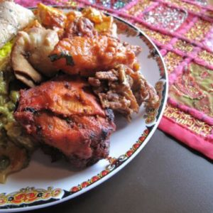 a plate with tandoori chicken, chili chicken and vegetable korm