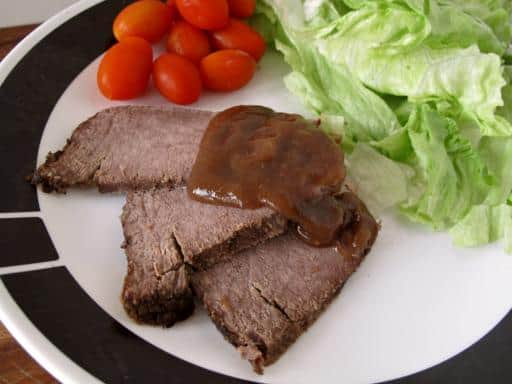 slices of pot roast with creamy gravy, sided with vegetables