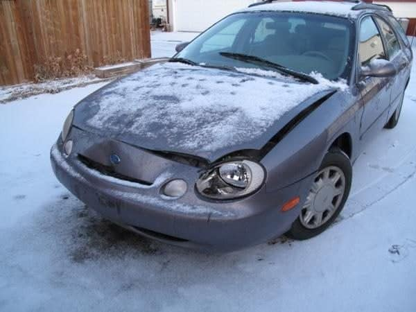 banged up black car with some snow