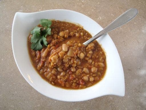 spicy lentil and bean soup in a white soup bowl with spoon